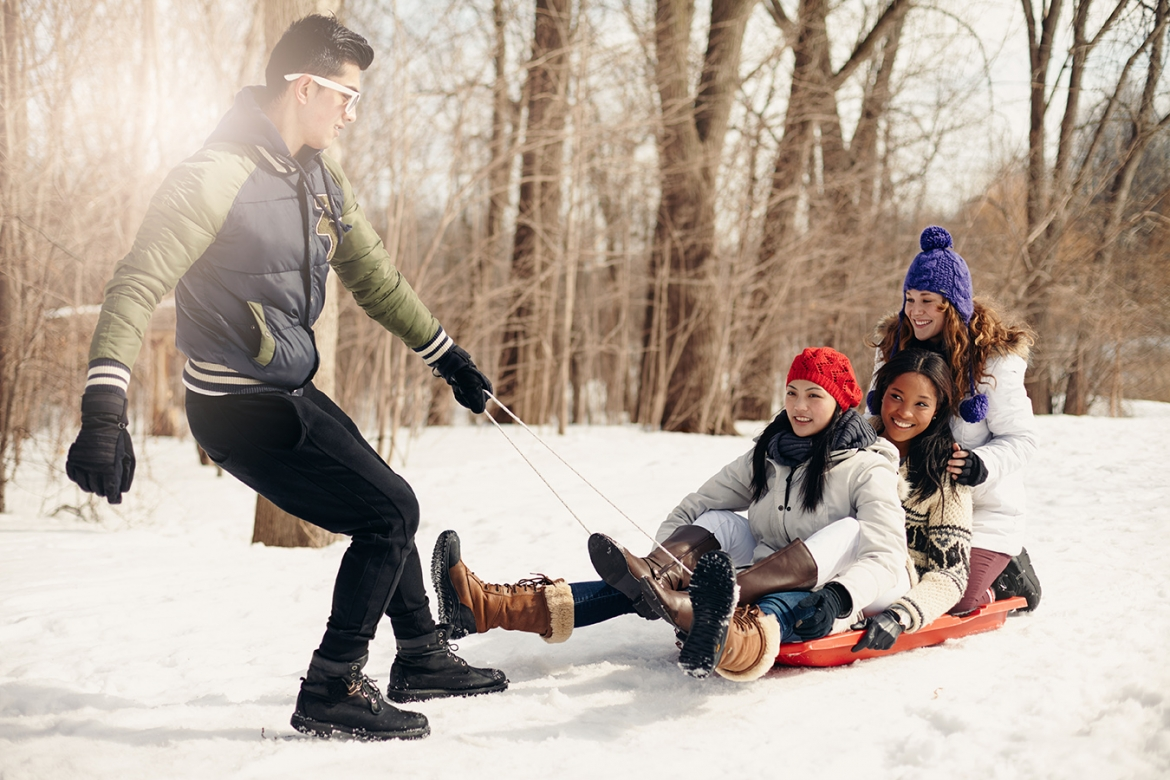 Group of friends enjoying pulling a sled in the snow